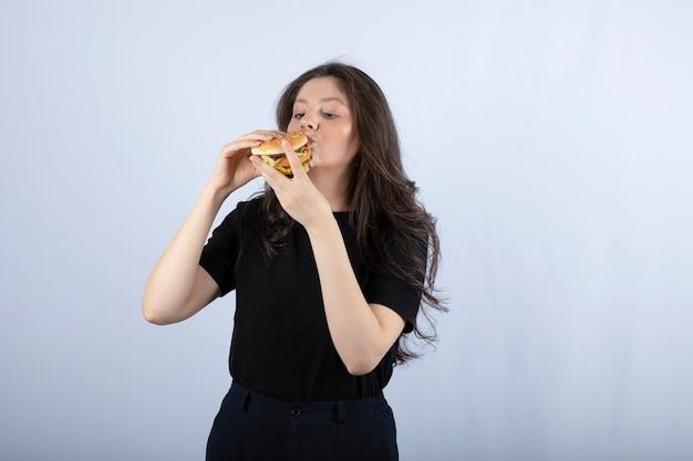 Belle jeune femme mangeant un délicieux hamburger de boeuf.