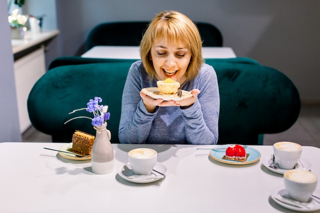 Belle jeune femme mangeant un dessert avec une bonne satisfaction. femme, séance, table, café desserts, café ou thé sur la table, réunion d'amis