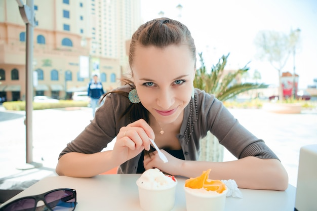 Belle jeune femme mangeant des glaces