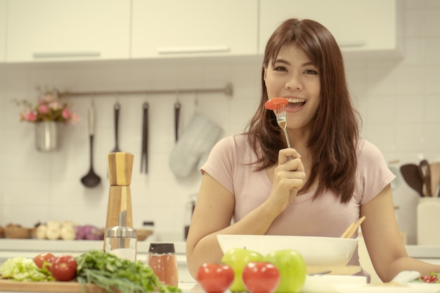 Belle jeune femme mangeant de la salade