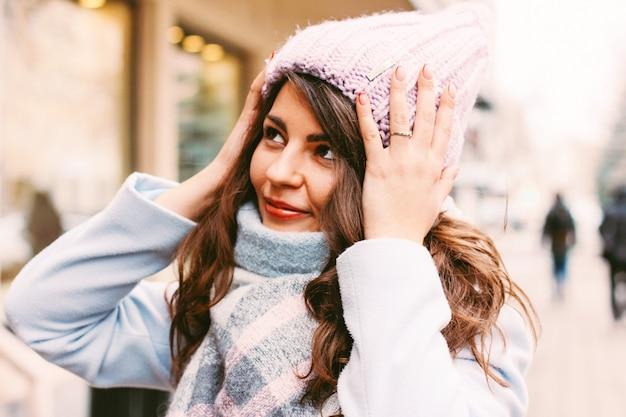 Belle jeune femme en manteau et chapeau en fin d'automne ou en hiver o