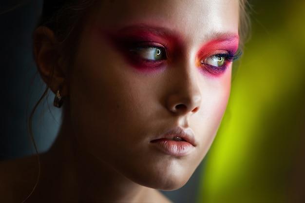 Belle jeune femme avec un maquillage artistique brillant