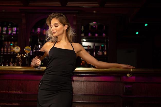 Belle jeune femme avec maquillage et coiffure dans une robe noire avec un verre de vin