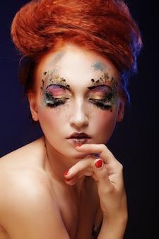 Belle jeune femme avec un maquillage coloré
