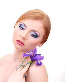 Belle jeune femme avec maquillage glamour et fleur, sur blanc