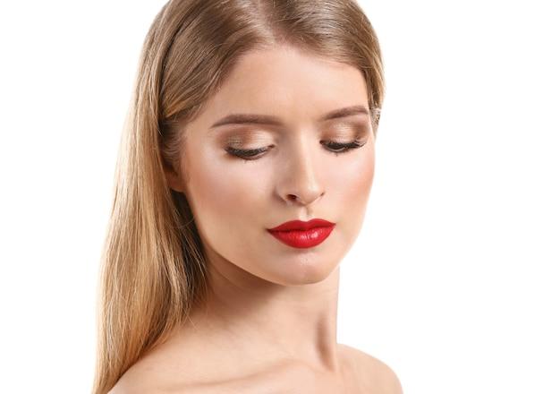 Belle jeune femme avec un maquillage lumineux sur blanc