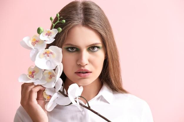 Belle jeune femme avec un maquillage lumineux et des fleurs sur la couleur