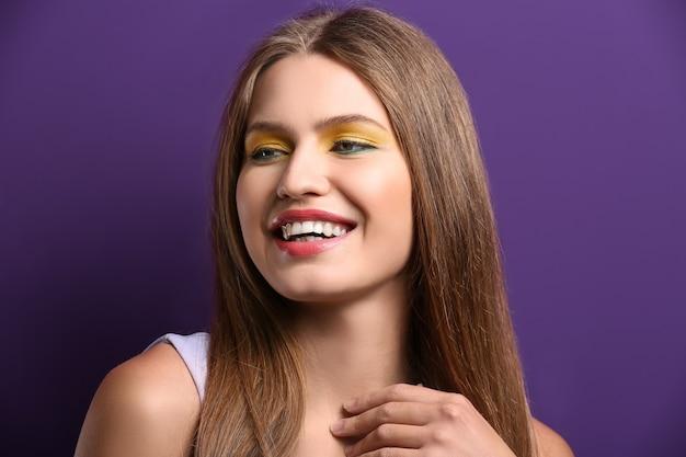 Belle jeune femme avec un maquillage lumineux sur la surface de couleur