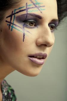 Belle jeune femme avec un maquillage lumineux