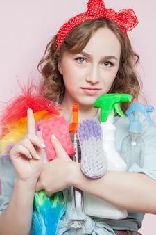 Belle jeune femme avec maquillage pin-up et coiffure avec des outils de nettoyage sur rose.