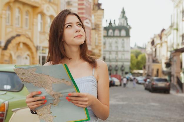Belle jeune femme marchant dans les rues de la ville avec une carte