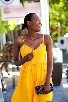 Belle jeune femme marchant à l'extérieur avec une fleur
