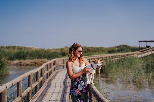 Belle jeune femme marchant sur une jetée en bois avec son chien