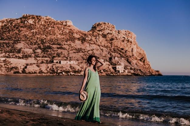 Belle jeune femme marchant sur la plage au coucher du soleil