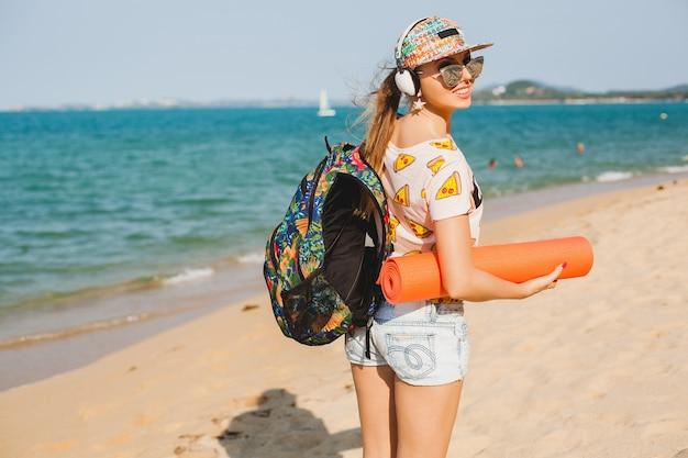 Belle jeune femme marchant sur la plage avec tapis de yoga, écouter de la musique sur les écouteurs, style swag sport hipster, short en jean, t-shirt, sac à dos, casquette, lunettes de soleil, ensoleillé, week-end d'été, joyeux