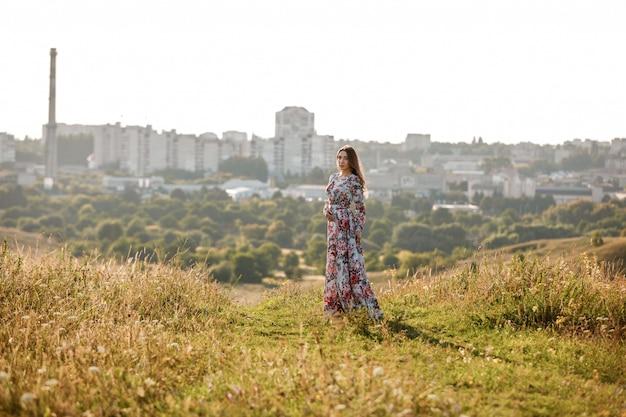 Belle jeune femme marche dans le champ d'été avec de l'herbe.