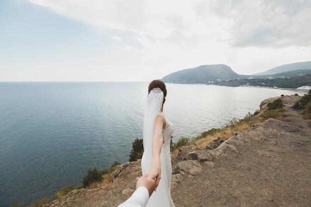 Belle jeune femme mariée tient la main d'un homme en plein air