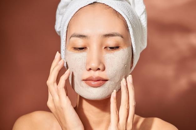 Belle jeune femme avec masque d'argile. cure thermale, soins personnels et peau saine