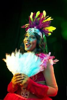 Belle jeune femme en masque de carnaval et costume de mascarade dans des lumières colorées