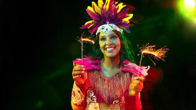 Belle jeune femme en masque de carnaval, costume de mascarade élégant avec plumes et cierges magiques invitant