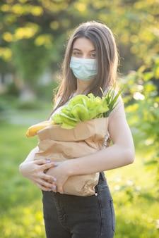 Belle jeune femme avec un masque dans le parc avec épicerie