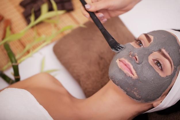 Belle jeune femme avec masque facial, cure thermale