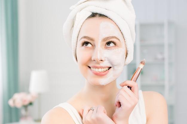 Belle jeune femme avec masque facial sur studio lumineux et mordant sa lèvre