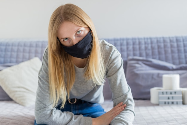 Belle jeune femme avec un masque noir assis sur le canapé et ayant des maux de tête. symptômes du coronavirus. fille triste blonde déprimée à la maison