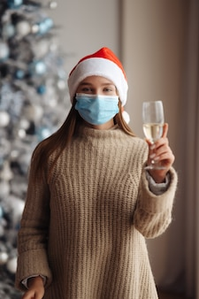 Belle jeune femme en masque de protection avec verre de champagne à la maison