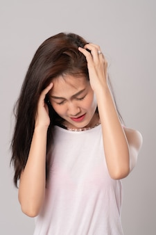 Belle jeune femme a des maux de tête; portrait de femmes d'affaires asiatiques graves ou migraine, triste, soins de santé et concept d'entreprise.