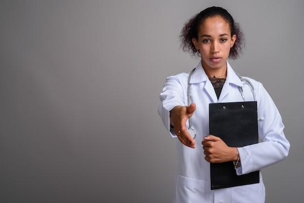 Belle jeune femme médecin africaine contre le mur gris