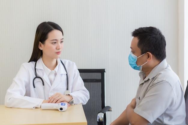 Une belle jeune femme médecin asiatique parle avec un patient de sa douleur et de ses symptômes