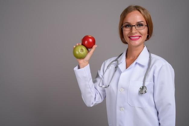 Belle jeune femme médecin aux cheveux blonds contre zone grise