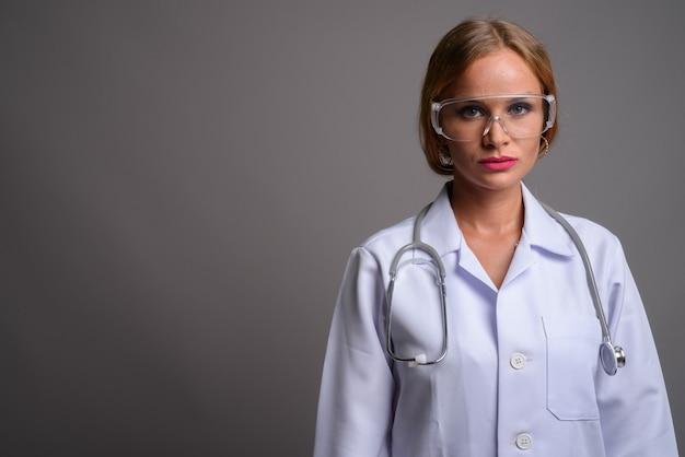 Belle jeune femme médecin aux cheveux blonds portant protection