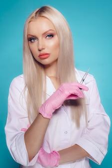 Belle jeune femme médecin esthéticienne en uniforme médical tenant la seringue sur blue. injection beauté et cosmétique