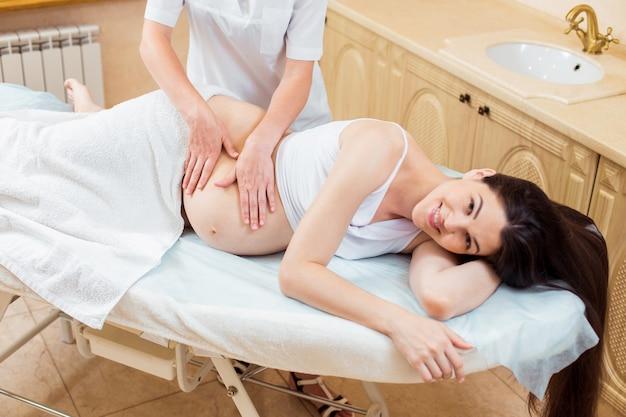 Belle jeune femme médecin massothérapeute dans une salle de cosmétologie faisant un massage à une fille enceinte aux cheveux longs