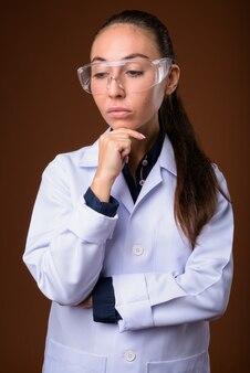 Belle jeune femme médecin portant des lunettes de protection sur fond marron