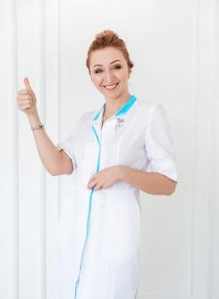 Belle jeune femme médecin posant dans une blouse blanche sur un fond de mur blanc et montrant la classe.