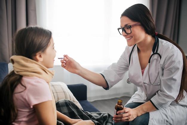 Belle jeune femme médecin souriant. elle donne du sirop sur une cuillère à un enfant malade. le docteur l'a dirigé dans la bouche de l'enfant. petite fille, gardez-le ouvert. ils sont dans une pièce.