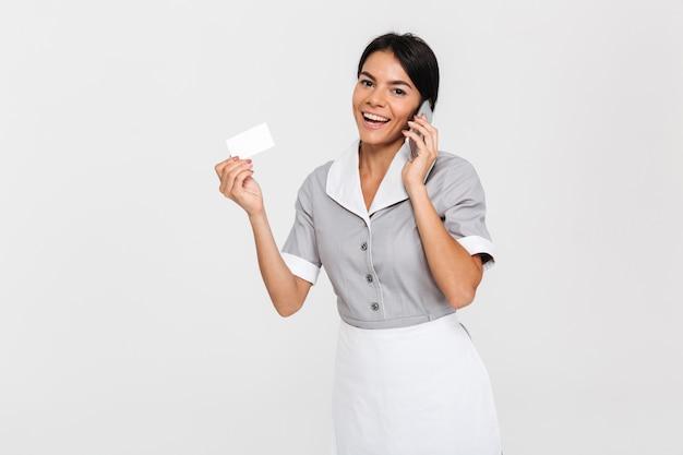 Belle jeune femme de ménage parler sur téléphone mobile en se tenant debout et montrant le pan coupé vide