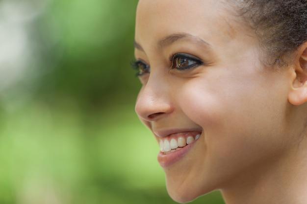 Belle jeune femme métisse au parc, portrait souriant