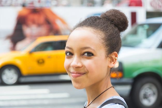 Belle jeune femme métisse dans la ville, souriant portrait