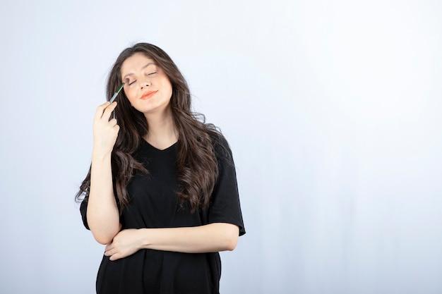 Belle jeune femme mettant l'ombre avec une brosse cosmétique sur un mur blanc.