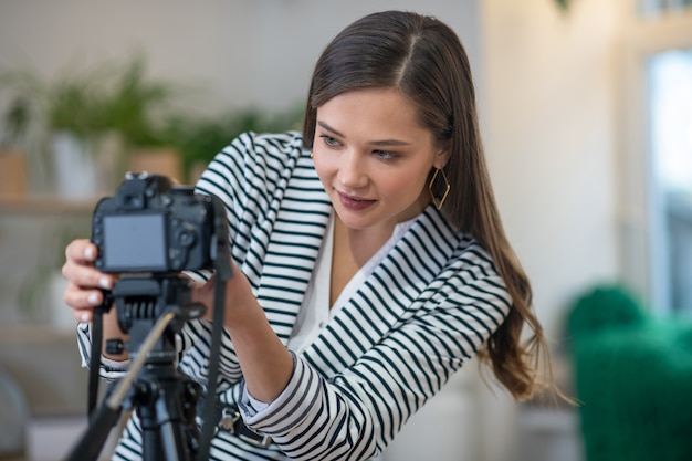 Belle jeune femme mettant en place l'appareil photo tout en étant prêt à tirer