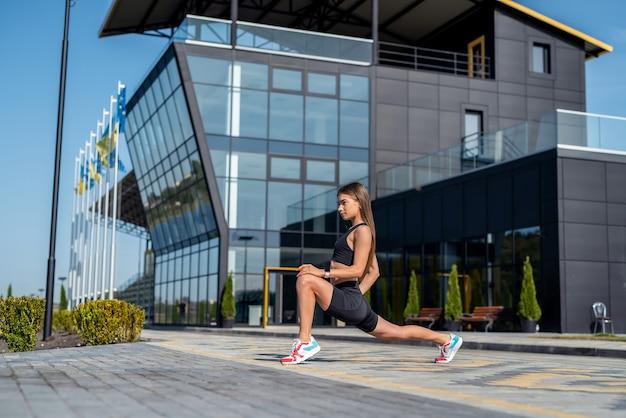 Belle jeune femme mince en sporwear, faire des exercices du matin près d'un bâtiment en verre moderne, mode de vie sain