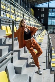 Belle jeune femme mince en tenue de sport se détendre près des sièges dans le stade