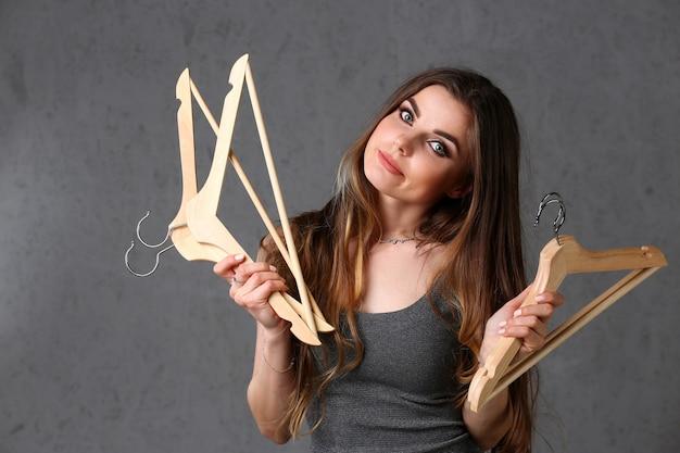 Belle jeune femme à la mode femme tenant des cintres en bois vides dans sa main avec une expression plus douce n'exprimant rien à porter des vêtements et aller montrer ou faire la fête avec d'autres amis.