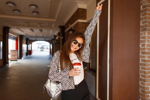 Belle jeune femme à la mode heureuse avec du café dans une veste élégante se promène dans la ville