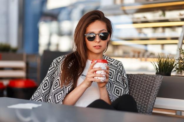 Belle jeune femme à la mode avec des lunettes de soleil dans un t-shirt blanc avec une veste de mode, boire du café à l'extérieur dans un café