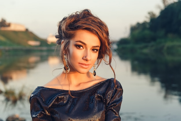 Belle jeune femme à la mode qui pose en robe à la côte de la rivière